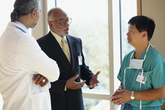 African businessman talking to male Asian surgeon and male African doctor Stock Photos