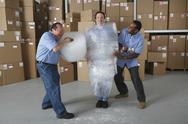 Three male warehouse workers joking around Stock Photos