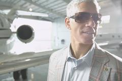 Middle-aged man next to airplane in hanger Stock Photos