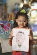 Young Hispanic girl holding artwork Stock Photos