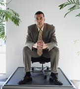 African American businessman sitting in chair on pedestal Stock Photos