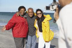 Group of middle-aged friends using video camera at beach Stock Photos
