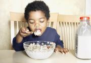 Stock Photo of Young African American boy eating cereal