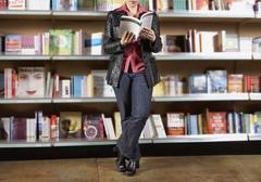 Woman reading book in bookstore Stock Photos