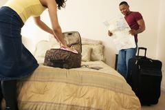 Afrikkalainen pari pakkaus matkalaukku sängyllä Kuvituskuvat