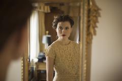 Woman wearing fancy dress looking in mirror Stock Photos