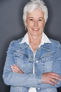 Senior woman in denim jacket smiling Stock Photos