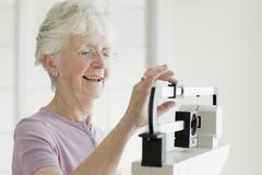 Senior woman weighing self on scale Stock Photos