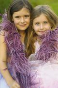 Two young girls wearing feather boa and smiling Stock Photos