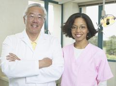 Senior Asian male dentist with African female dental assistant Stock Photos