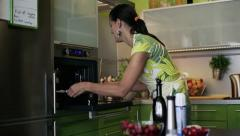 Happy woman puts cupcakes on pan into oven HD Stock Footage