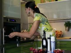 Happy woman puts cupcakes on pan into oven NTSC Stock Footage