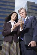 Businesswoman and businessman looking at PDA in urban scene Stock Photos