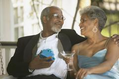 Senior African couple in formal dress with gift and cocktail Stock Photos