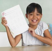 Asian girl holding up school paper with A+ Stock Photos