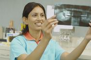 Indian female dental assistant looking at x-rays Stock Photos