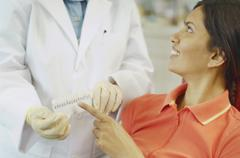 Dental patient choosing tooth color sample from dentist Stock Photos