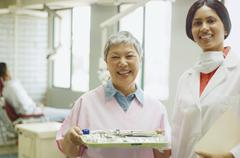 Indian female dentist and senior Asian female dental assistant smiling Stock Photos