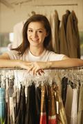 Woman leaning on rack at clothing store Stock Photos