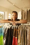 African woman leaning on rack at clothing store Stock Photos