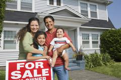 Hispanic family with For Sale sign in front of house Stock Photos