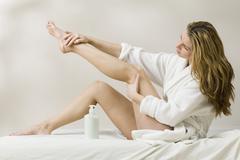 Hungarian woman applying lotion to leg Stock Photos