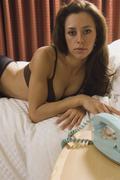 Semi-nude Hispanic woman laying on bed Stock Photos