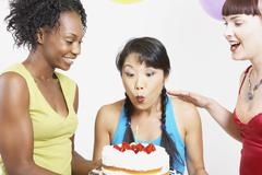 Asian woman blowing out candle on cake Stock Photos