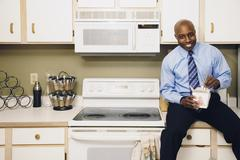 African man eating take out food in kitchen Stock Photos