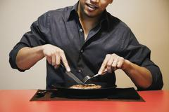Asian man cutting meat on plate Stock Photos