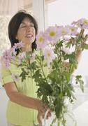 Senior woman arranging flowers in vase Stock Photos