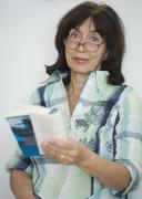 Senior woman wearing eyeglasses and reading Stock Photos