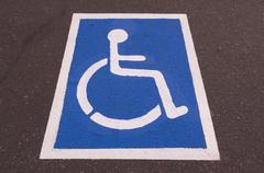 Handicapped symbol painted on pavement Stock Photos