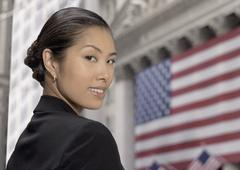 Asian businesswoman in front of American flag - stock photo