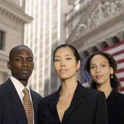 Portrait of businesspeople in front of American flag - stock photo