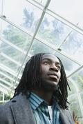Low angle view of African man in greenhouse Stock Photos