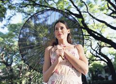 Hispanic woman carrying parasol Stock Photos