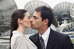 Hispanic couple kissing in front of satellite dishes Stock Photos