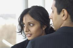 Middle Eastern businesswoman looking over man's shoulder - stock photo