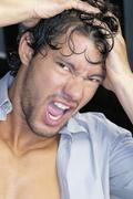 Close up of young man yelling with hands on head Stock Photos