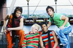 Group of teenage boys sitting on bench near bumper cars Stock Photos