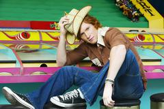 Male teenager with straw hat sitting on stool at carnival booth Stock Photos