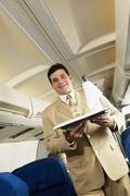 Low angle view of Hispanic male flight attendant carrying wine on a tray Stock Photos
