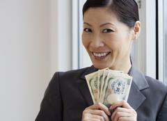 Middle-aged Asian businesswoman holding yen banknotes Stock Photos