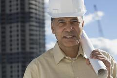 African male contractor with blueprints in urban scene Stock Photos