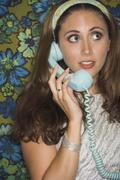 Young woman in retro outfit using telephone Stock Photos