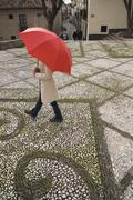 High angle view of woman walking with umbrella in urban setting Stock Photos