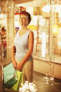 Hispanic woman with shopping bags looking in shop window Stock Photos