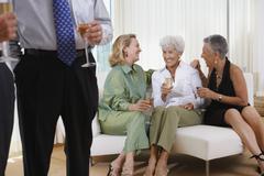 Three senior women talking on sofa at party Stock Photos