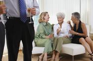 Stock Photo of Three senior women talking on sofa at party